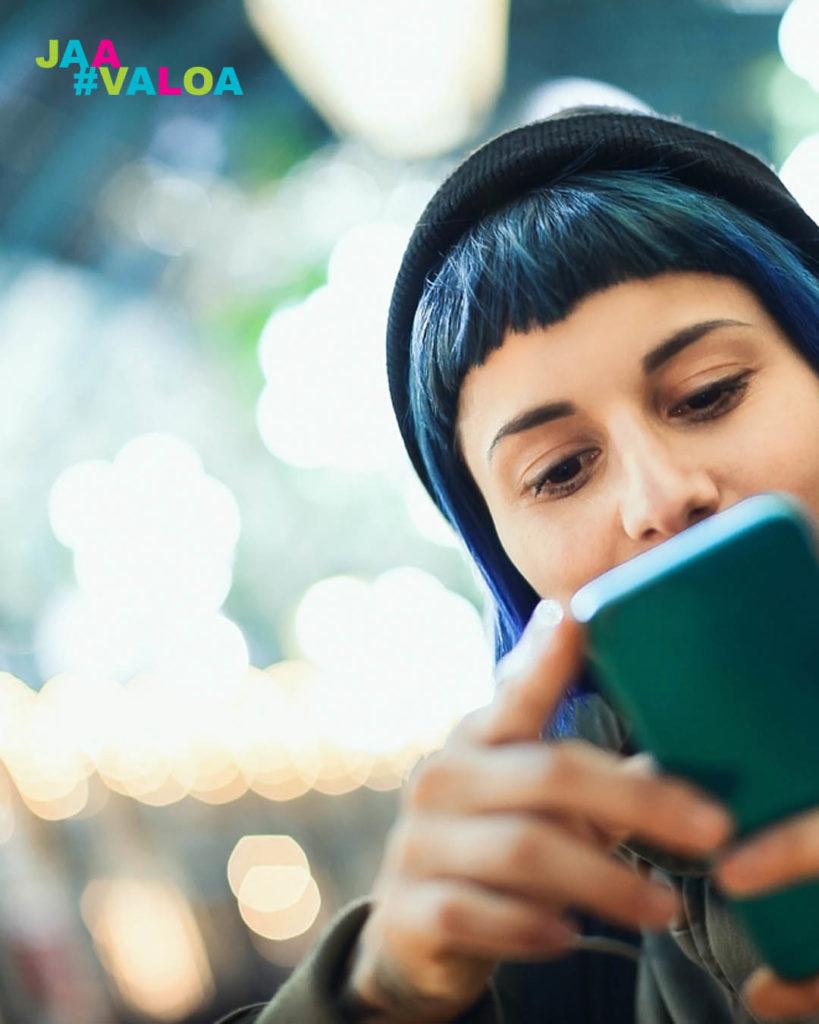 Tyttö lukee kännykän ruutua
